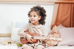 Kleines Mädchen spielt Ukulele